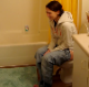 A girl is video-recorded by her friend as she sings and takes a shit while sitting on a toilet. We assume her pain and breakup is with her own poop leaving her asshole. There is an audible plop sound, and she has some singing talent as well.