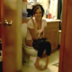 A girl is seen through an open bathroom door taking a shit on the toilet.