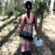 A brunette woman takes a shit on a plate outdoors.