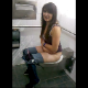 A brunette girl is video-recorded pissing while sitting on a toilet.