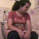 A brunette girl with a big bottom tells us how much she loves to eat beans. She proceeds to eat her bowl of beans while sitting on a toilet. Some bodily functions are audible, so we assume she pooped. No poop is actually seen. Over 4 minutes.
