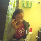 A black girl is seen peeing while sitting on a toilet and then wiping herself, dropping the toilet paper roll in the process. We are not sure if this is genuine voyeur because she appears to be looking at the camera.
