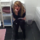 A blonde, British girl is video-recorded sitting on a toilet. We are not sure if she is peeing or pooping.