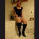 An attractive blonde girl takes a shit on the bathroom floor while leaning against a bath tub.