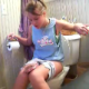 An attractive blonde girl has some trouble taking a shit while sitting on a toilet. She grabs hold of the bathroom walls as she strains to get her turd out. We are not sure how successful she was, but she does have to wipe her ass when finished.