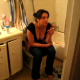 A very brief video clip of a girl smoking while pooping on the toilet. She quickly closes the door when she realizes that she is on camera.
