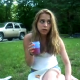 A cute girl with blonde hair is sitting in the grass eating when all of a sudden she blows a stinky, silent fart. The fart makes her get out of there, and proceeds to act silly for the rest of the video clip.