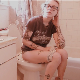 A blonde girl with tattoos and wearing glasses records herself shitting and pissing  while sitting on a toilet. Audible plop sounds. Video has vintage sepia color tones. Product and dirty TP shown. 720P HD. Over 2 minutes.