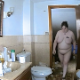 A hidden camera records a fat, butch-looking woman with tattoos taking a piss and a shit while sitting on a toilet and then wiping her ass. A plop is heard over her pissing. About a minute.