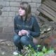 An attractive girl is secretly video-recorded as she takes a piss and a shit outdoors by a brick wall - probably in Eastern Europe. There is no audio, but we can see a piss stream and a turd dropping out from between the foliage.