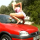 A blonde woman pisses on the hood of a red car. I guess it is better than a bird shitting on it!