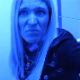 A mature, blonde woman records herself taking a shit while sitting on a toilet in a public restroom. No poop action or product is seen, but a soft-sounding dump is heard in several waves. Video has an odd, bluish hue. Over 5 minutes.