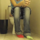A hidden camera is set up on a bathroom floor to record a girl with unmatched socks taking a piss and a shit while sitting on a toilet. Plops are audible. About 7 minutes.