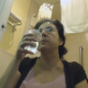 An older, mature woman wearing glasses drinks some water, pisses (with visible piss stream), and then finally takes a shit while sitting on a toilet. Audible poop sounds, but no product is seen. Presented in 720P HD. Over 4 minutes.