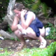 A woman is voyeuristically  recorded relieving herself in an outdoor location. She may be pissing or shitting, but it is difficult to determine from the distance. presented in 720P HD. About 2 minutes.