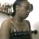 A black woman video-records herself from the chest up as she takes wet, runny shits while sitting on a toilet in several scenes. About 4 minutes long.