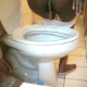 A black girl video-records herself shitting into a toilet in three scenes.
