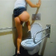 A woman takes a shit while standing over a hospital toilet. She misses the bowl, and her turd lands on the seat before finally sliding in on its own. She wipes her ass and shows us the mess. About 3 minutes.