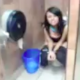 A Spanish girl is video recorded using a toilet in a public bathroom and hamming it up for the camera in this low resolution, small video clip.