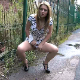 An attractive, blonde, European girl takes a piss and farts in an outdoor, public location.