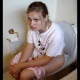 A cute European girl is video-recorded straining and taking a shit while sitting on a toilet. Pooping and peeing sounds are clearly heard.