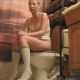 A blonde girl sits on a toilet and has some wet farts and some diarrhea. When finished, she gets up, cleans her has with her hands after wetting them in the sink, and towel dries her ass.