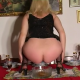 A blonde woman poops into a crystal bowl while squatting over a nicely appointed dinner table.