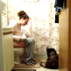 A girl sitting on a toilet and her dog battle for space in the bathroom.