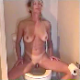 An attractive blonde woman pees while sitting on a toilet, and then wipes herself.