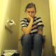 A hidden camera is set up on the floor of a bathroom and records a pretty girl taking a piss and a shit while sitting on a toilet. Plopping sounds are heard. She sneezes and wipes her nose as well. About 5.5 minutes.