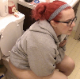 A girl with red-dyed hair and wearing glasses takes a runny-sounding shit while sitting on a toilet at home. She wipes her ass and looks at her dirty TP. About 4.5 minutes.