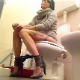 A short-haired brunette girl wearing heels and a dress sits down on a toilet and immediately farts and pisses. About a minute into the clip, some very subtle pooping sounds can be heard. She sits there for a while before wiping. Over 3.5 minutes.