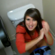 A pretty brunette girl gets quickly embarrassed as she is video-recorded while sitting on a toilet in a public restroom trying to poop.