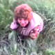 Some kids video record their mother peeing (maybe pooping) while squatting in the grass in this small, low-resolution video clip.