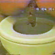 An older, lower quality video clip features a woman sitting on a toilet backwards and taking a shit in three scenes.