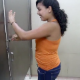An American, Hispanic girl is video-recorded by her friend as she visits the public restroom at Wal-Mart to take a piss.