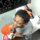 A black girl is video-recorded by her friends sitting on a toilet in a public restroom. She may be peeing or pooping. There are no sounds to indicate which.