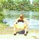 "From the classic ""Outdoor Pooping Paradise"" sold by GP.Com - a girl squats on the ground beside a scenic lake and takes what seems to be a never-ending, rope of a shit!"