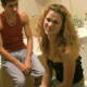 An Eastern-European video featuring a pretty girl farting repeatedly while sitting on a toilet with her skirt partially pulled down. A guy in the background sniffs her farts, and they both start laughing at the ridiculousness of the scene.