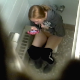 A hidden camera mounted in the ceiling records a blonde girl taking a piss and a shit in a public restroom while texting on her phone. Plop sounds are audible, but no poop is visible. Presented in 720P HD video. About 4.5 minutes.