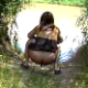 A woman takes a shit on the ground in a natural, outdoor setting.