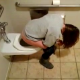 A girl is secretly recorded by her friend as she pisses into a toilet at a public restroom.