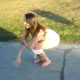 A girl is video-recorded by her friends as she takes a piss on the street.