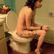 A skinny girl with tattoos and punky red and green hair takes a piss and a shit while sitting on a toilet in 2 scenes. Plopping sounds are more noticeable in the second scene. Presented in 720P HD. About 7 minutes.