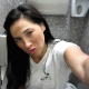 An attractive brunette woman records herself shitting into a toilet in a public restroom stall. Pooping sounds are fully audible. Presented in 720P HD video.