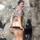 A beautiful, European, brunette girl takes a piss and a long, soft shit on a rocky landscape by a beach. About 4 minutes.