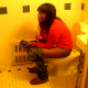 A black girl is video recorded as she takes a shit in a public restroom. Clip is very brief, and no audible pooping sounds can be heard.
