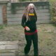 A woman with multi-colored hair takes a huge shit while squatting in her own back yard.