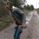 A woman takes a shit on a gravel road in the rain.