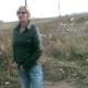 A woman wearing sunglasses takes a shit outside along the railroad tracks - probably somewhere in Europe.